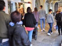 走在商店窗口前面和购物在16世纪的中央门廓的人们 免版税库存图片