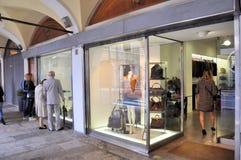 走在商店窗口前面和购物在16世纪的中央门廓的人们 免版税库存照片