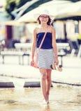 走在喷泉的逗人喜爱的矮小的青少年女孩在热的夏日 免版税库存图片
