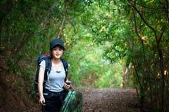走在国立公园的徒步旅行者年轻女人户外与背包 妇女游人去的野营在森林里 免版税图库摄影