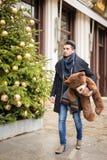 走在圣诞节的街道上的英俊的人与女用连杉衬裤是 库存照片