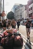 走在垃圾袋子附近的人们倾销在牛津街,伦敦,英国 库存照片