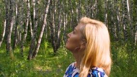 走在城市公园和享受夏日的愉快的白肤金发的妇女 配置文件视图 影视素材