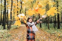 走在城市公园的秋天女孩 愉快的可爱和美丽的少妇画象在秋天颜色的森林里 免版税库存图片