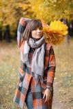 走在城市公园的秋天女孩 愉快的可爱和美丽的少妇画象在秋天颜色的森林里 免版税库存照片