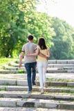年轻走在城市的夫妇妇女和人停放握手 免版税库存照片