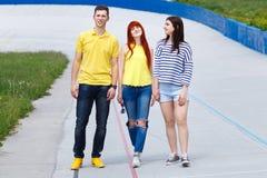 走在城市的小组三个年轻朋友 库存图片