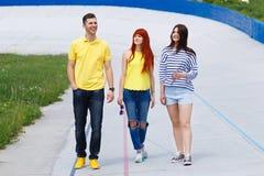 走在城市的小组三个年轻朋友 免版税图库摄影