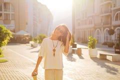 走在城市的快乐的妇女在春天早晨 免版税库存图片