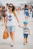 年轻走在城市的母亲和她的儿子 免版税库存照片