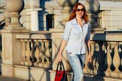走在城市的红头发人女孩 她是微笑和无忧无虑的 便装样式 免版税库存图片