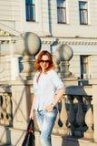 走在城市的红头发人女孩 她是微笑和无忧无虑的 便装样式 库存图片