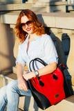 走在城市的红头发人女孩 她是微笑和无忧无虑的 C 库存照片
