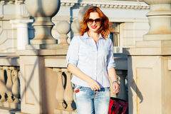 走在城市的红头发人女孩 她是微笑和无忧无虑的 C 图库摄影