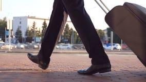 走在城市街道上和拉扯在轮子的成功的商人的脚手提箱 年轻男性企业人的腿 股票录像