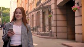 走在城市街道上和拿着电话,微笑的年轻俏丽的姜妇女,拿着在一肩膀的背包 股票视频