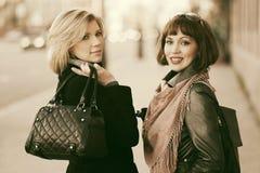 走在城市街道上的两名年轻时尚妇女 库存图片