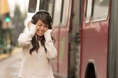 走在城市街道上的妇女盖她的耳朵 免版税库存照片