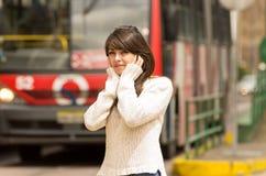 走在城市街道上的妇女盖她的耳朵 免版税库存图片