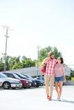 走在城市街道上的富感情的夫妇反对清楚的天空 免版税库存图片