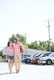 走在城市街道上的富感情的夫妇反对清楚的天空 免版税库存照片
