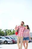 走在城市街道上的愉快的夫妇反对清楚的天空 免版税库存图片