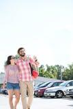 走在城市街道上的愉快的夫妇反对清楚的天空 库存照片