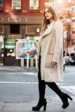 年轻走在城市街道上的adul美丽的妇女穿有灰色夹克的偶然街道样式秋天服装 免版税图库摄影