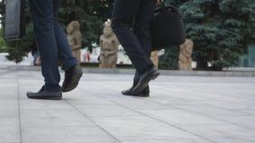 走在城市街道的两个商人的脚 商人通勤  确信的人在他的途中 股票录像