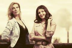 走在城市街道的两名年轻时尚妇女 库存照片