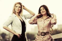 走在城市街道的两名愉快的年轻时尚妇女 库存图片