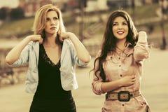 走在城市街道的两名愉快的年轻时尚妇女 图库摄影
