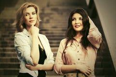 走在城市街道的两名年轻时尚妇女 免版税图库摄影