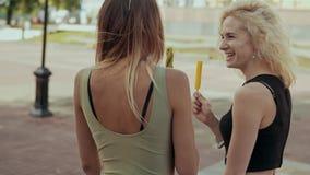走在城市街道的逗人喜爱的妇女朋友吃在慢动作的冰淇凌 股票视频
