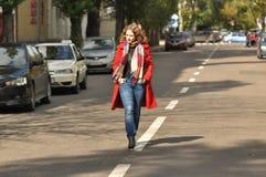 走在城市道路的美丽的女孩 免版税库存图片
