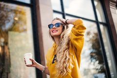 走在城市附近的年轻美丽的白肤金发的饮用的咖啡 芥末sweetshot 都市背包,摆在反对的明亮的红色嘴唇 免版税图库摄影
