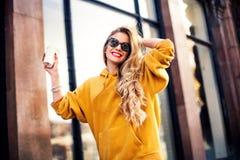 走在城市附近的年轻美丽的白肤金发的饮用的咖啡 芥末sweetshot 都市背包,摆在反对的明亮的红色嘴唇 免版税库存图片