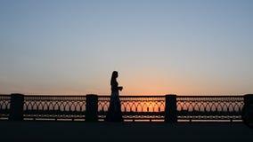走在堤防附近栏杆在夏天和喝从一纸杯的女孩 剪影在日落的晚上 股票录像