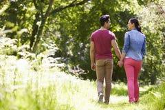 走在夏天乡下的年轻夫妇背面图  图库摄影