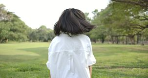 走在夏天公园的一名年轻可爱的亚裔妇女的特写镜头在日落,她努力去做并且转动回到神色在 影视素材