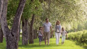 走在夏天公园的愉快的家庭在开花的苹果树附近 父亲、母亲和两个女儿花费时间 股票视频
