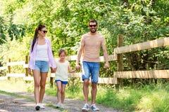 走在夏天公园的愉快的家庭 免版税库存图片