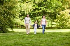 走在夏天公园的愉快的家庭 库存照片