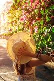 走在夏天庭院和嗅到的九重葛花里的少妇在日落 免版税库存图片