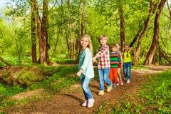 走在夏天森林里的孩子握手 库存照片