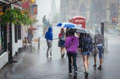 走在夏天雨的小组女孩在城市 免版税图库摄影