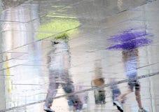 走在多雨的两个人模糊的反射剪影  免版税库存照片