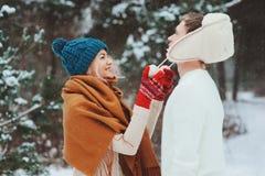 走在多雪的冬天森林里的愉快的年轻爱恋的夫妇,盖用雪和拥抱 库存照片