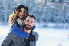 走在多雪的冬天森林里的愉快的爱恋的夫妇,花费圣诞节一起假期 室外季节性活动 免版税库存图片