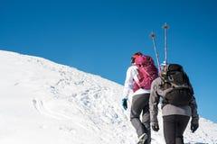 走在多雪的山的夫妇 免版税库存照片